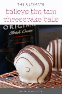 A close up of white chocolate coated balls drizzled with milk chocolate in front of a bottle of Irish cream.