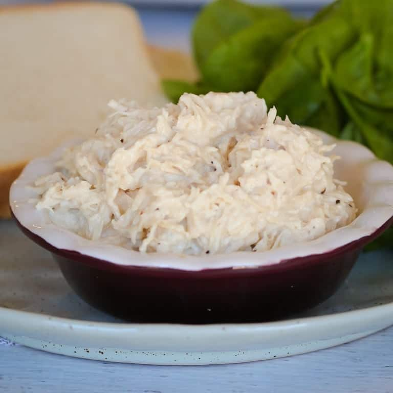 Steamed and shredded white chicken breast meat in a bowl.
