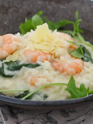 Shredded parmesan on top of a risotto filled with prawns and rocket leaves in a bowl.