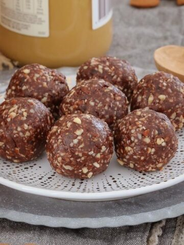 7 Bliss Balls sitting  on a grey pattered plate on a bench.