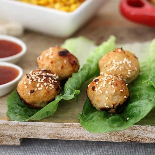 Baked chicken meatballs sprinkled with sesame seeds, resting on cos lettuce leaves
