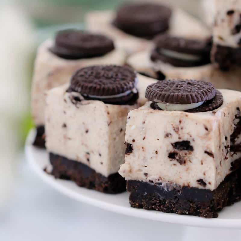 An Oreo biscuit on the top of each square of a chocolate cheesecake slice made with crumbled Oreo biscuits