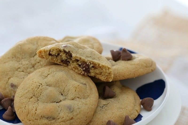 A pile of cookies made with chocolate chips, with a half eaten one on top