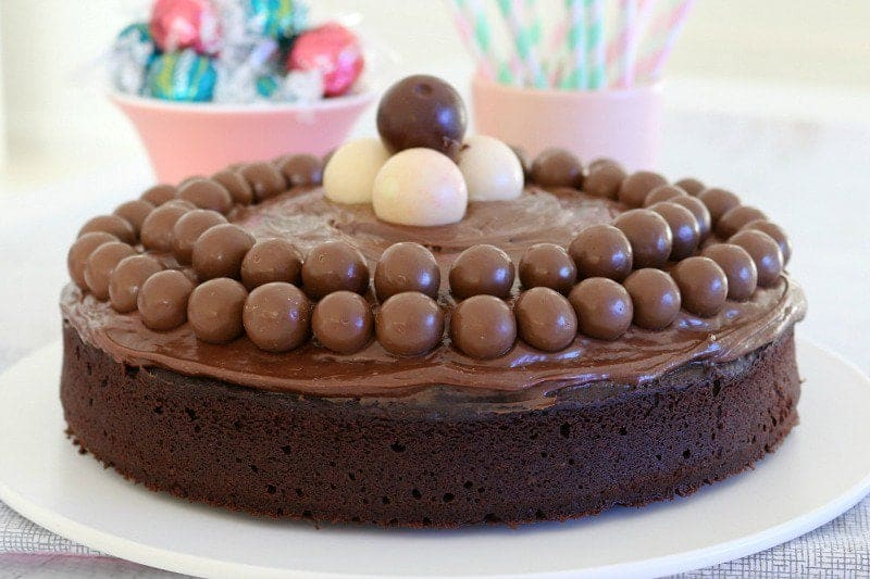 A chocolate cake with chocolate frosting, decorated with white and milk chocolate balls on top.