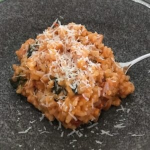 Grated parmesan on top of a tomato and bacon risotto in a bowl