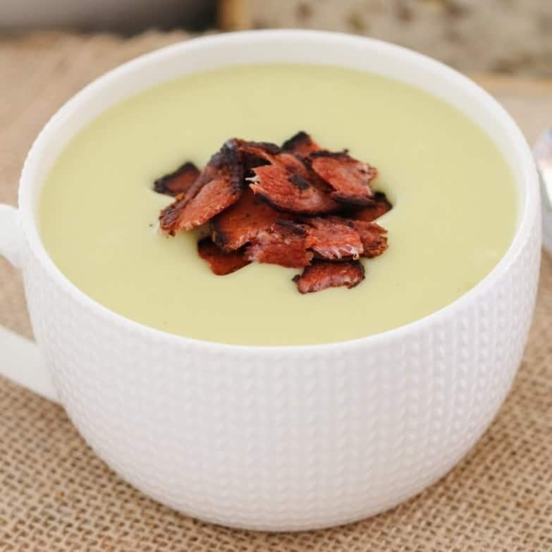 A creamy white potato and leek soup in a mug with crispy pieces of bacon on top.
