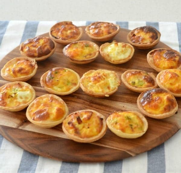 A wooden round chopping board with mini quiches sitting on top, sitting on a grey and white tea towel.