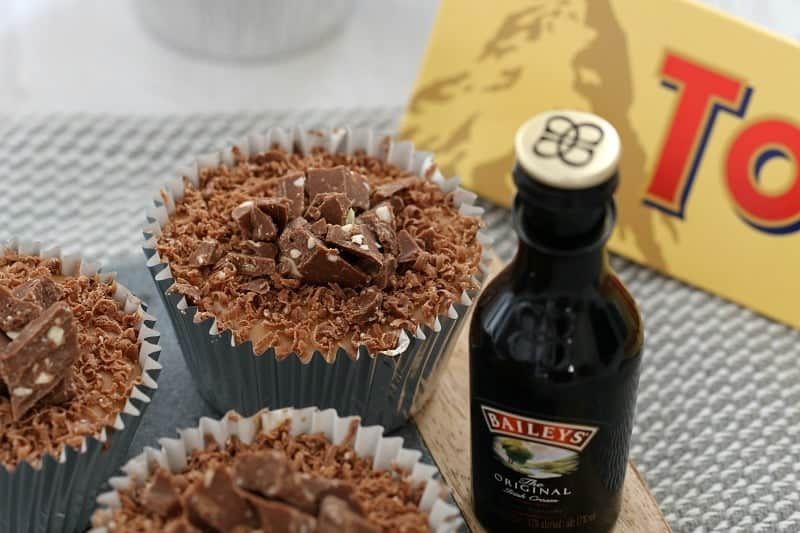 Individual chocolate cheesecakes in silver cupcake cases with crumbled Toblerone on top, and a small bottle of Baileys beside