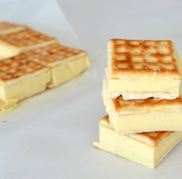 3 pieces of No Bake Lattice Slice stacked on top of one another in the for ground and 3 pieces sitting on a white bench in the back ground.