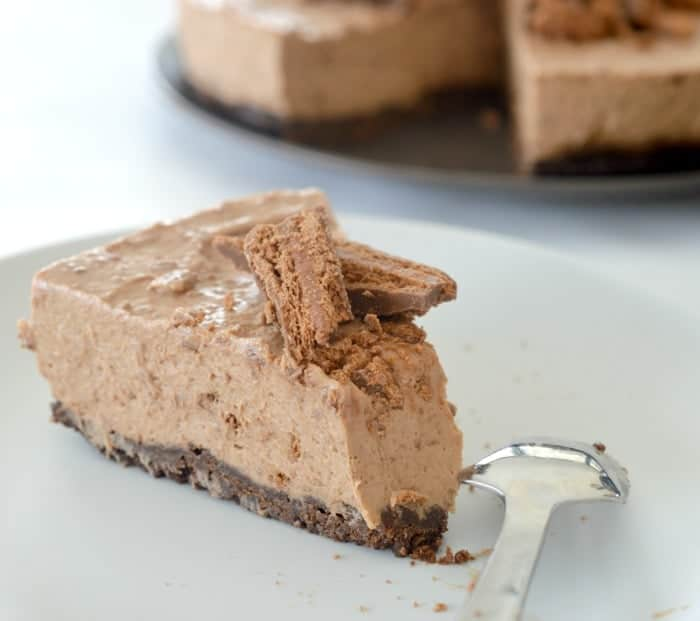 A serve of chocolate cheesecake with Tim Tam biscuits crumbled on top.