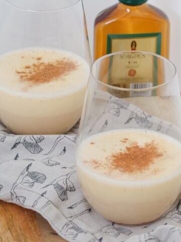 Two glasses, half filled with a milky eggnog drink sprinkled with nutmeg, and a small bottle of brandy in the background
