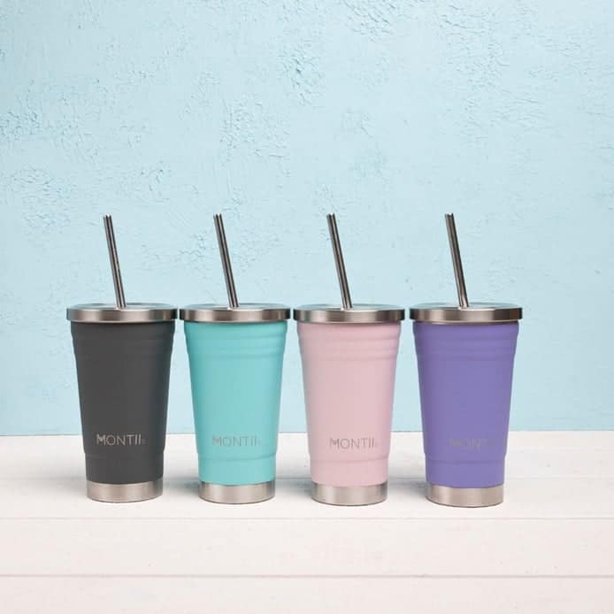 Four different coloured smoothie cups with straws on a bench