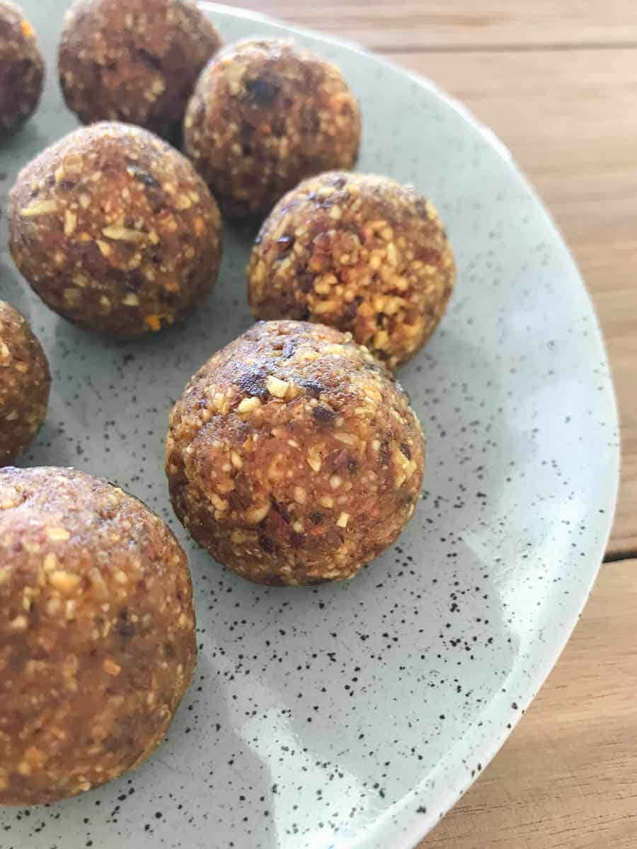 Small round healthy bliss balls made with chocolate and orange on a speckled grey dish