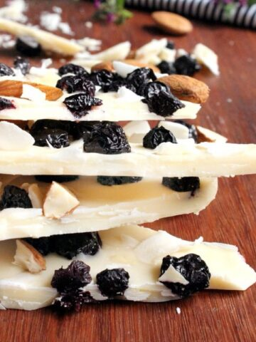 Chopped almonds and dried blueberries on wedges of white chocolate bark