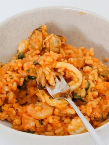 A fork in a white bowl filled with a risotto made with seafood