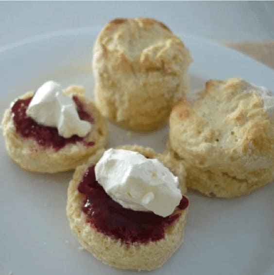 Scones on a plate with two halves spread with jam and cream
