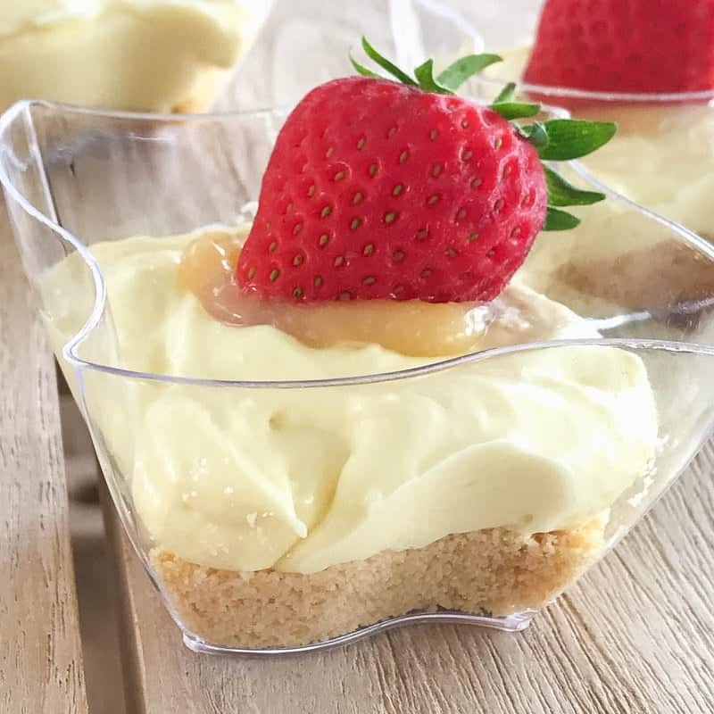 An individual lemon cheesecake in a glass bowl with a fresh strawberry on top