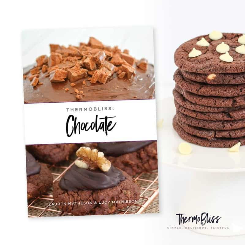 The cover of a recipe book with text Thermomix Chocolate, next to a stack of double chocolate cookies
