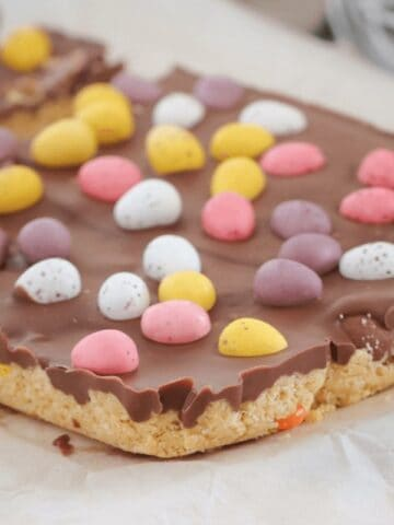A slice topped with milk chocolate and mini Easter eggs on a bench