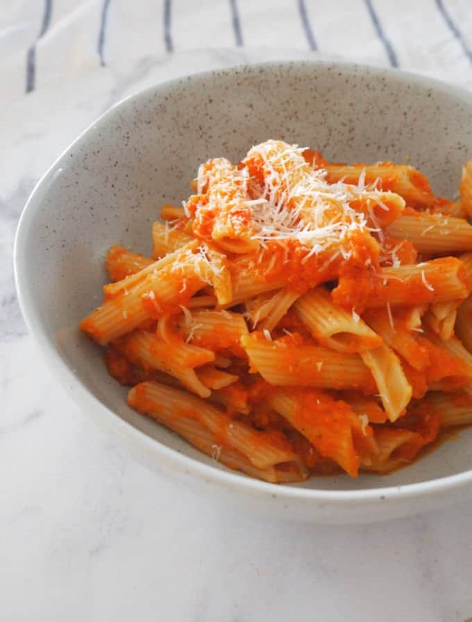 A bowl filled with penne in a light tomato based sauce, with finely grated parmesan on top
