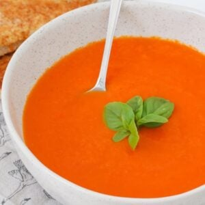 A bowl with a spoon, filled with a creamy red tomato soup and a sprig of basil on top.