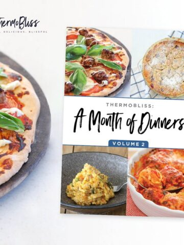 A pizza next to a ThermoBliss recipe book 'A Month of Dinners Vol 2'