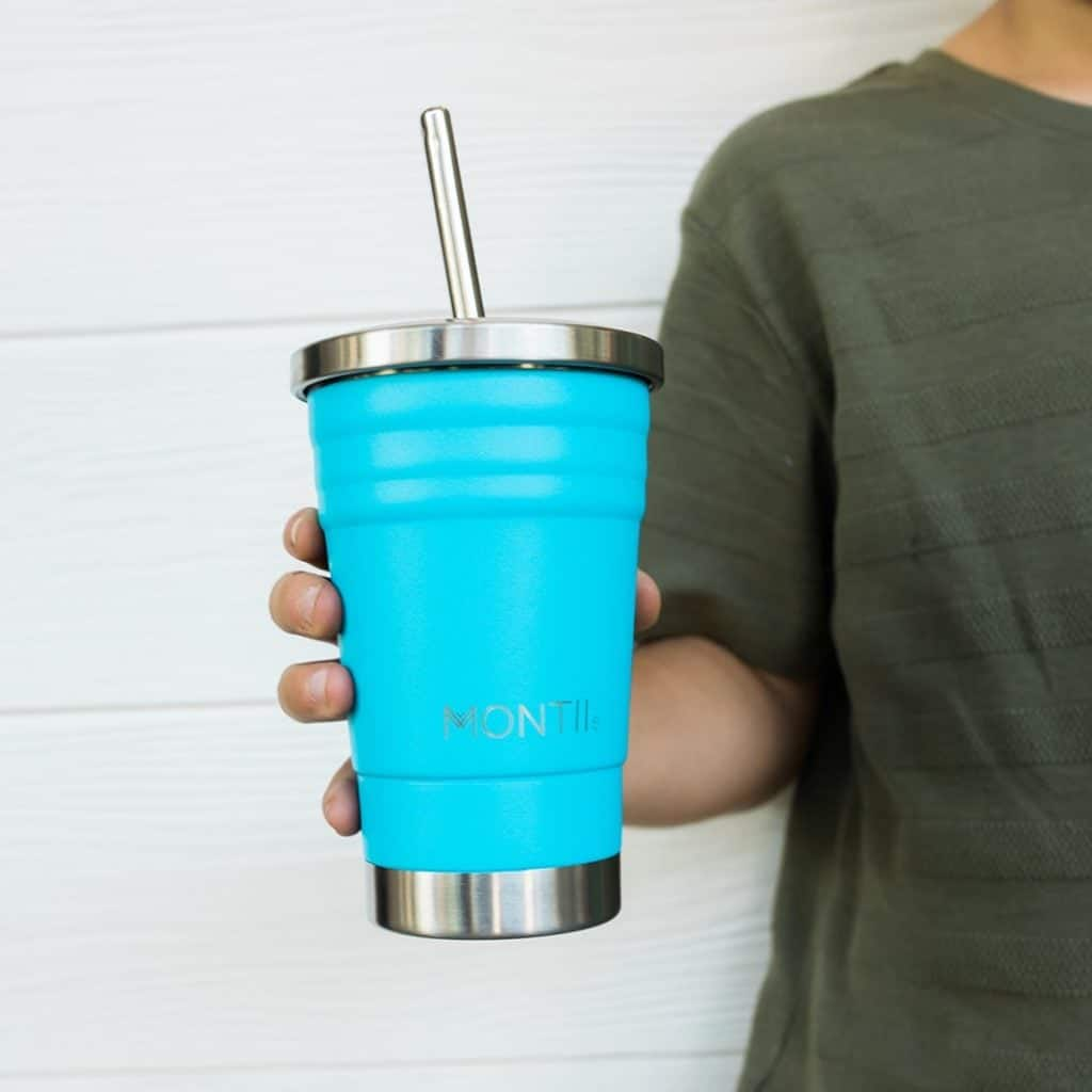 A boy holding a blue smoothie cup and straw
