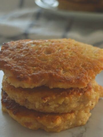 A stack of pikelets made with apple and oats on a bench