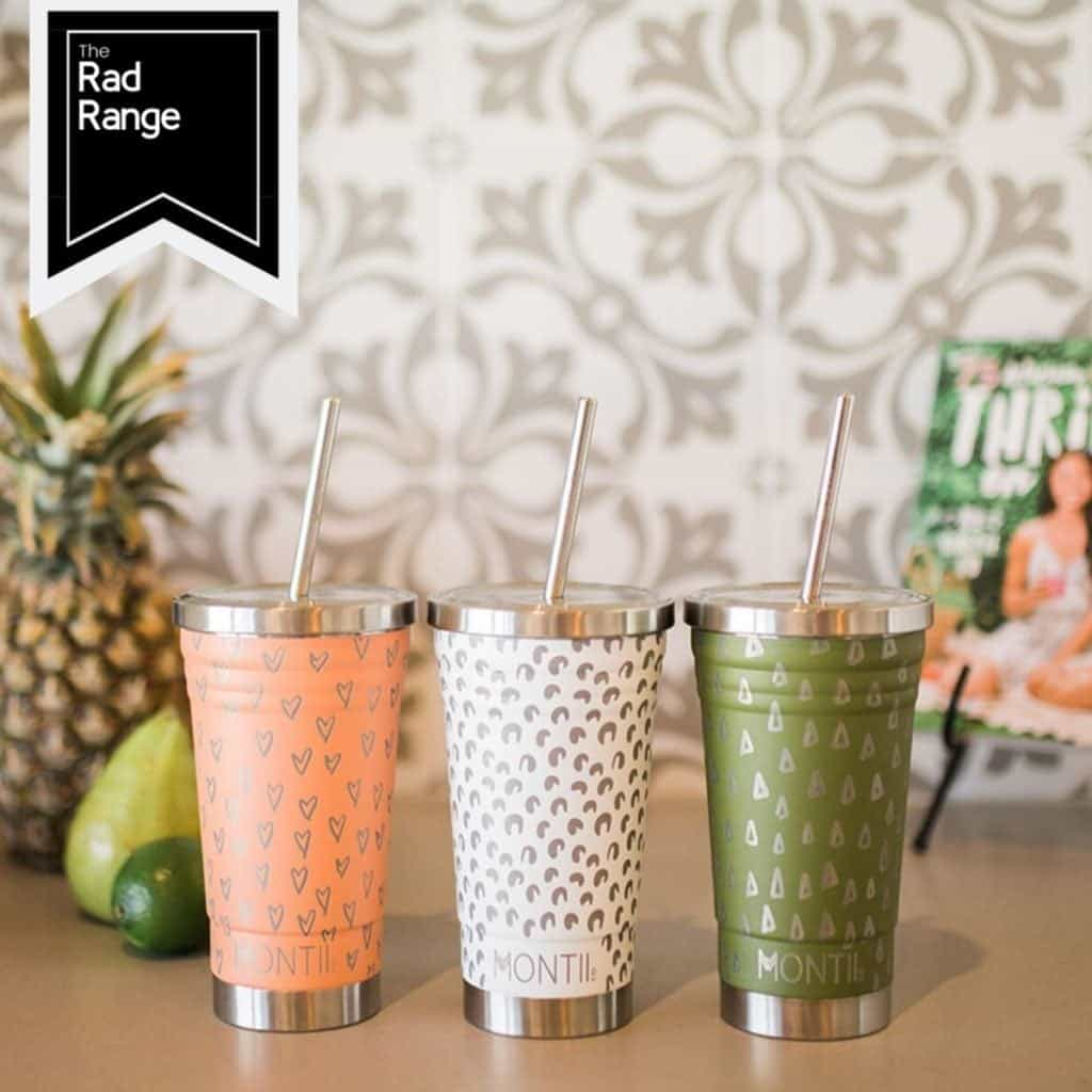 Three colourful smoothie cups with straws on a bench
