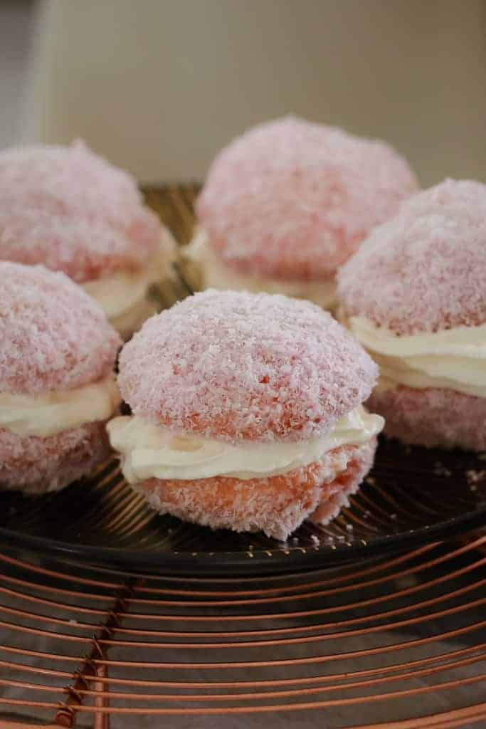 A plate of raspberry jelly cakes coated in coconut.