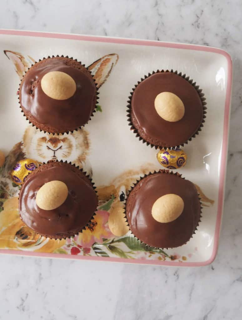 An overhead shot of four muffins with chocolate icing and a mini Caramilk Easter egg on top
