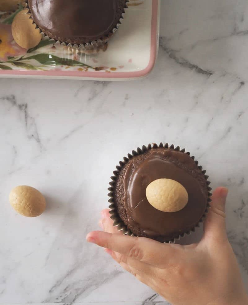 A hand holding a chocolate muffin with chocolate icing and a mini Caramilk Easter egg on top