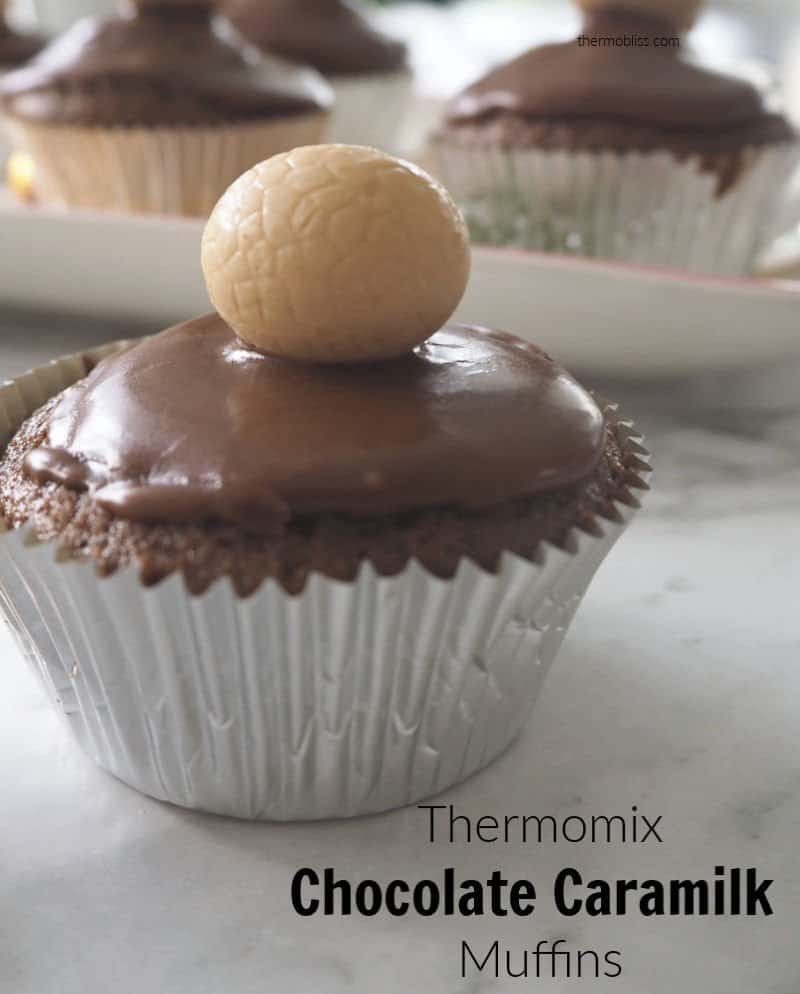 A chocolate muffin in a silver case with chocolate icing and a round lolly on top