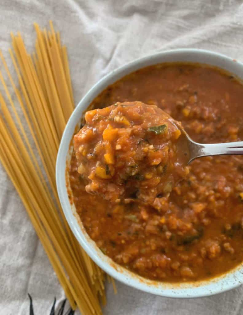 A spoon in a bowl of chunky bolognese sauce