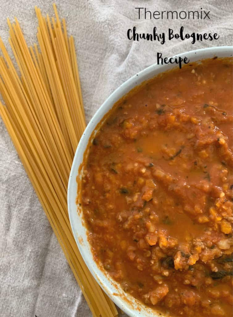 A bowl of bolognese sauce with a handful of  dry spaghetti beside