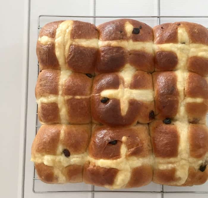 A batch of fruity Hot Cross Buns baked together and resting on a wire rack.