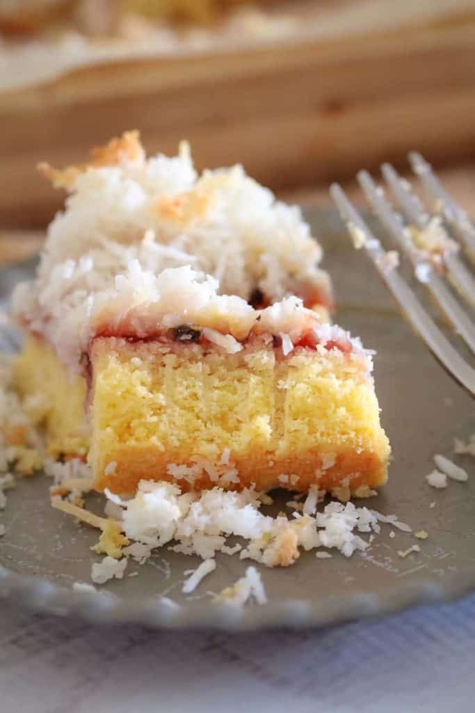 A baked coconut and jam slice on a plate.