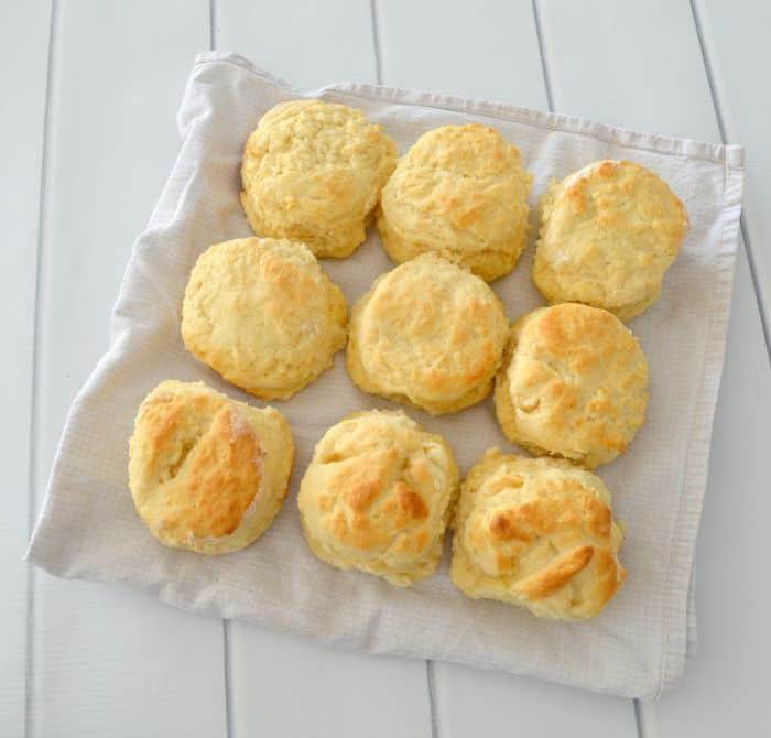A batch of nine freshly baked scones on a white tea towel.