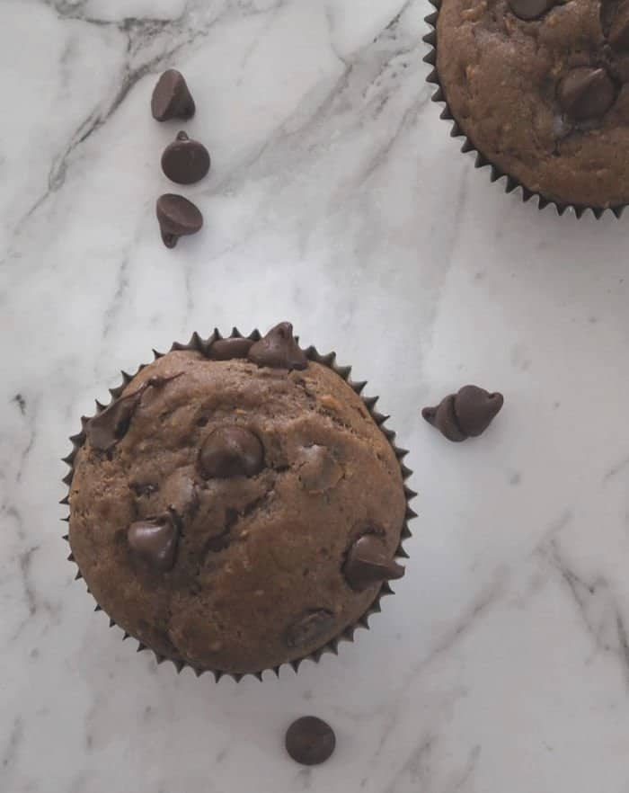 An overhead shot of chocolate muffins studded with chocolate chips on a marble bench.