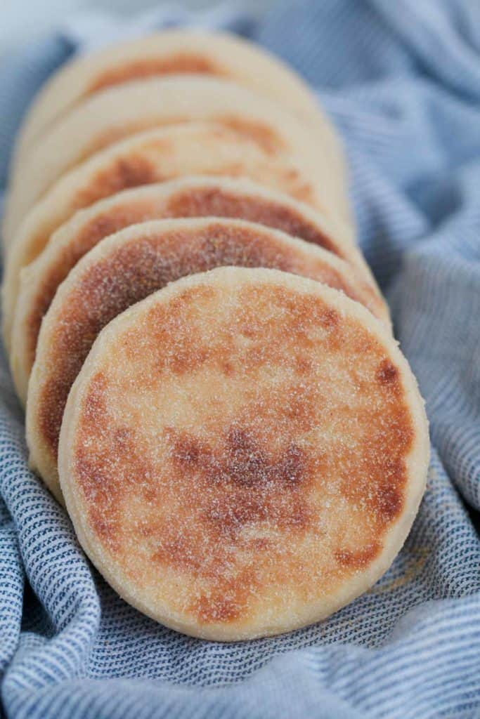 A line of homemade English muffins on a blue tea towel.