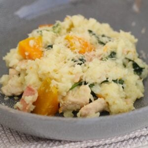A bowl of risotto with pumpkin, chicken, bacon and spinach.