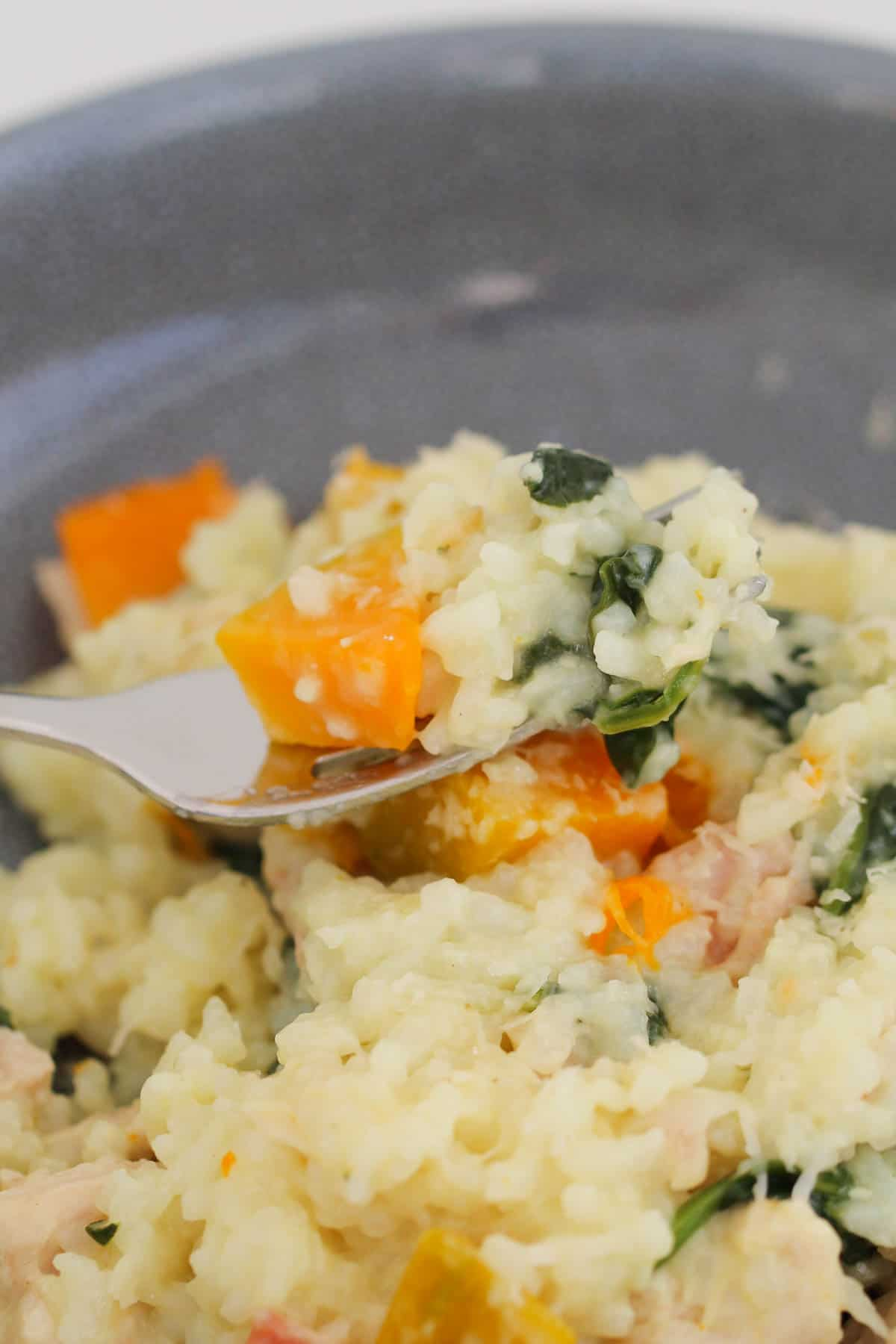 A fork of risotto with pumpkin and spinach.