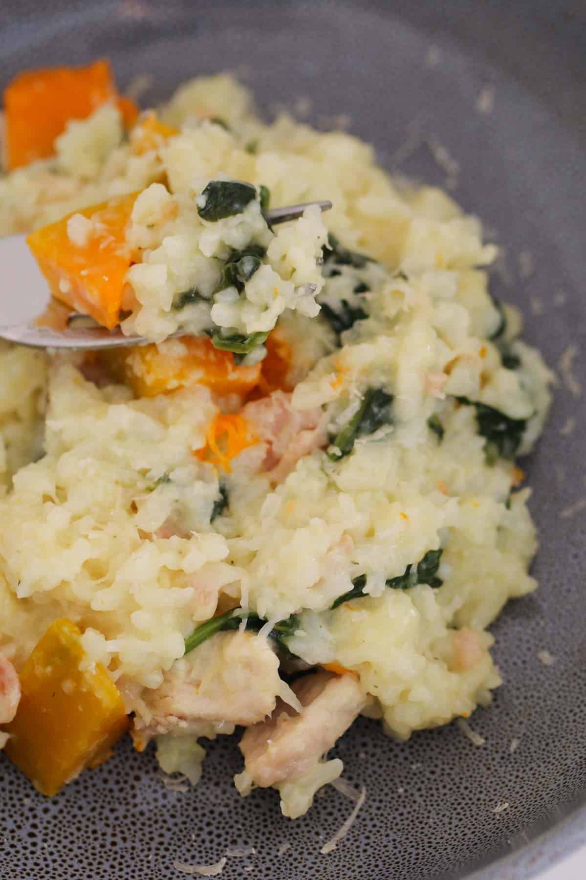 A forkful of chicken risotto with spinach and pumpkin.,