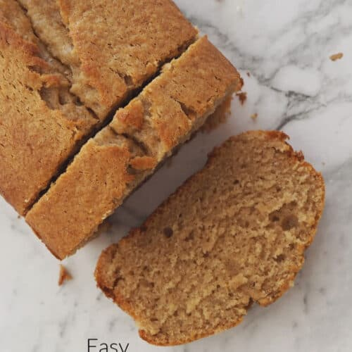 An overhead shot of a loaf of banana bread with two slices cut