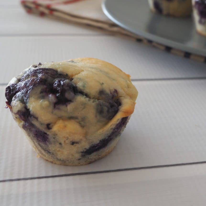 A close up of a baked muffin with lots of blueberries mixed through it.