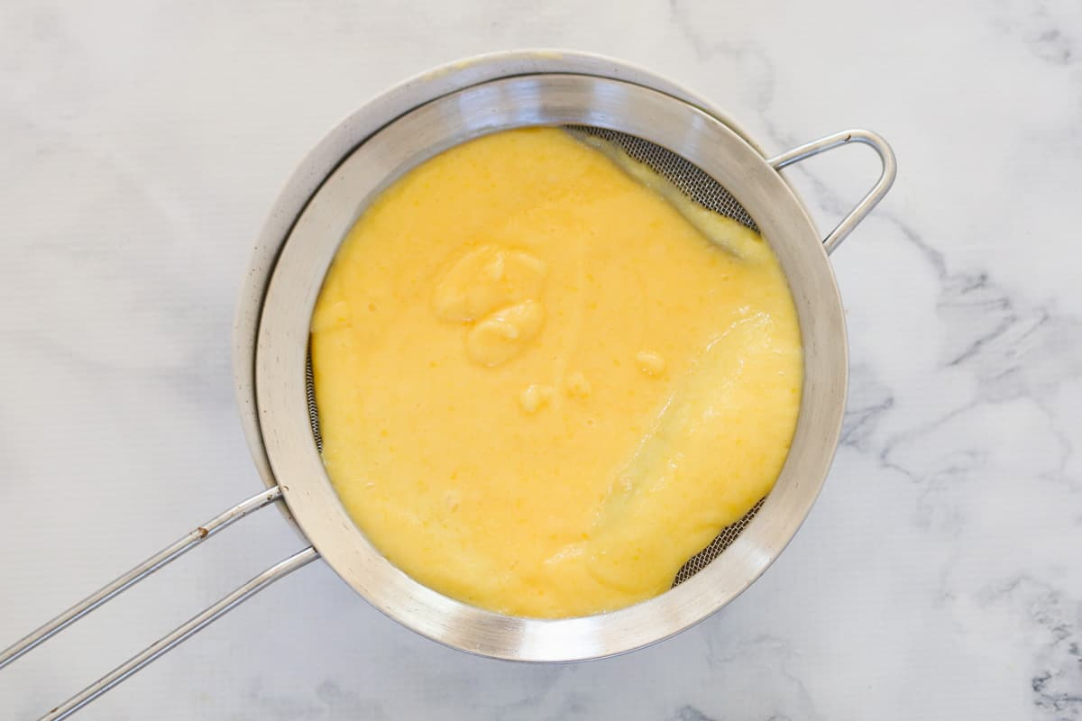 Lemon curd in a silver strainer.