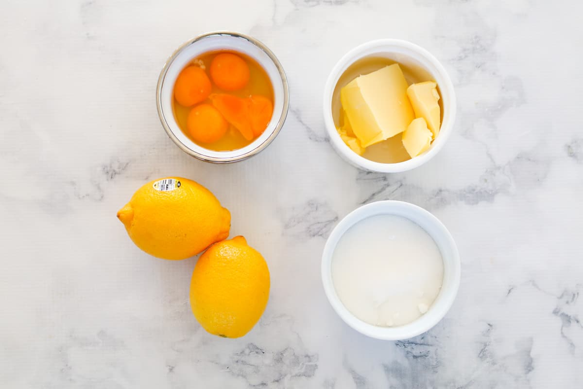 Butter, sugar, lemons and eggs in bowls.