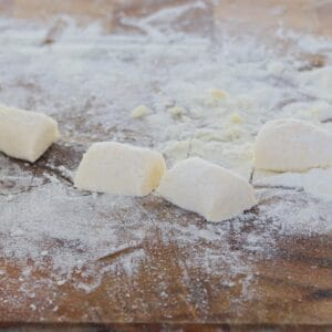 Homemade gnocchi on a floured wooden board.