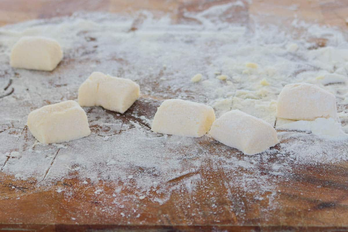 Homemade gnocchi cut into pieces on a floured board.