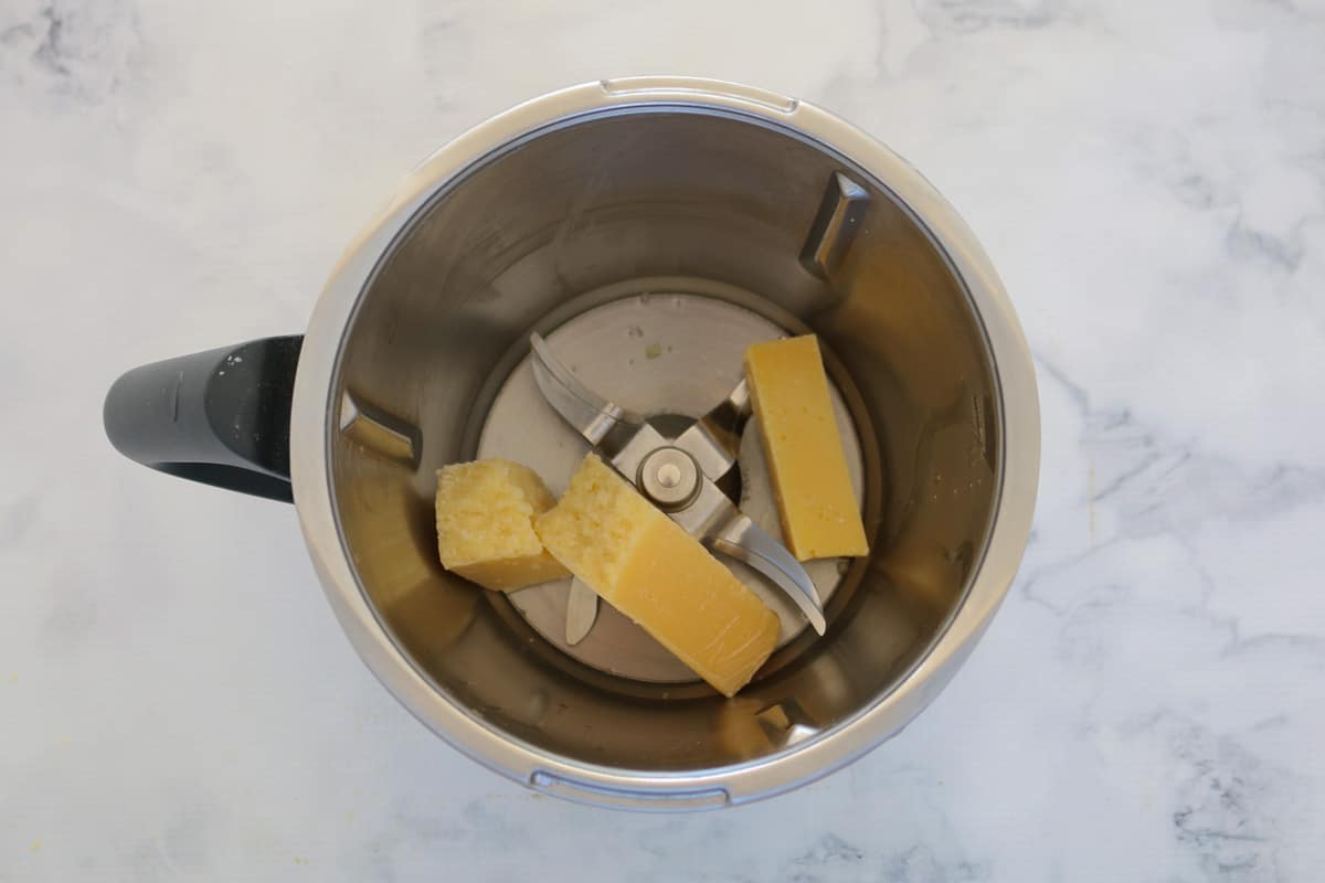 Chunks of parmesan cheese in a Thermomix bowl.